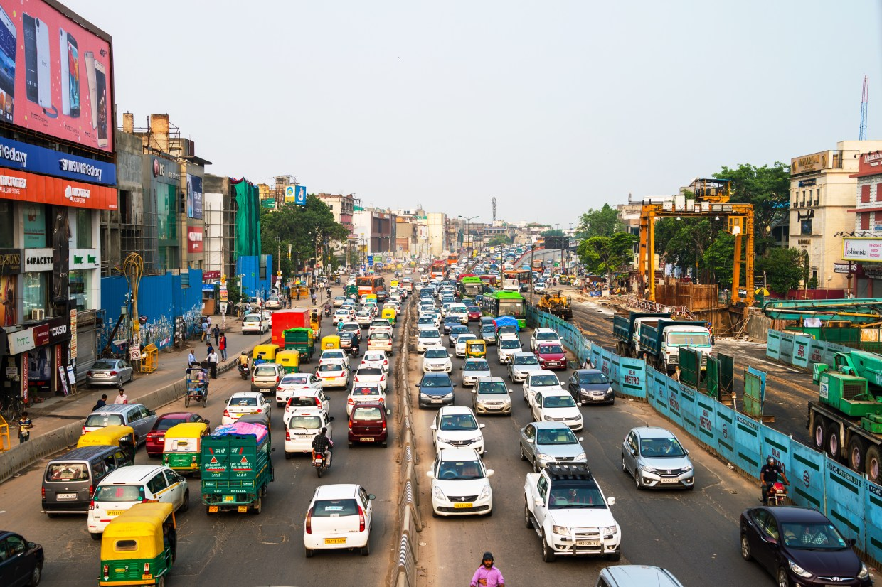 DELHI, INDIA - JULY 5, 2016: Heavy road traffic in the city center of Delhi, India. Buses and construction nearby the road. Various shops, cafes, restaurants
