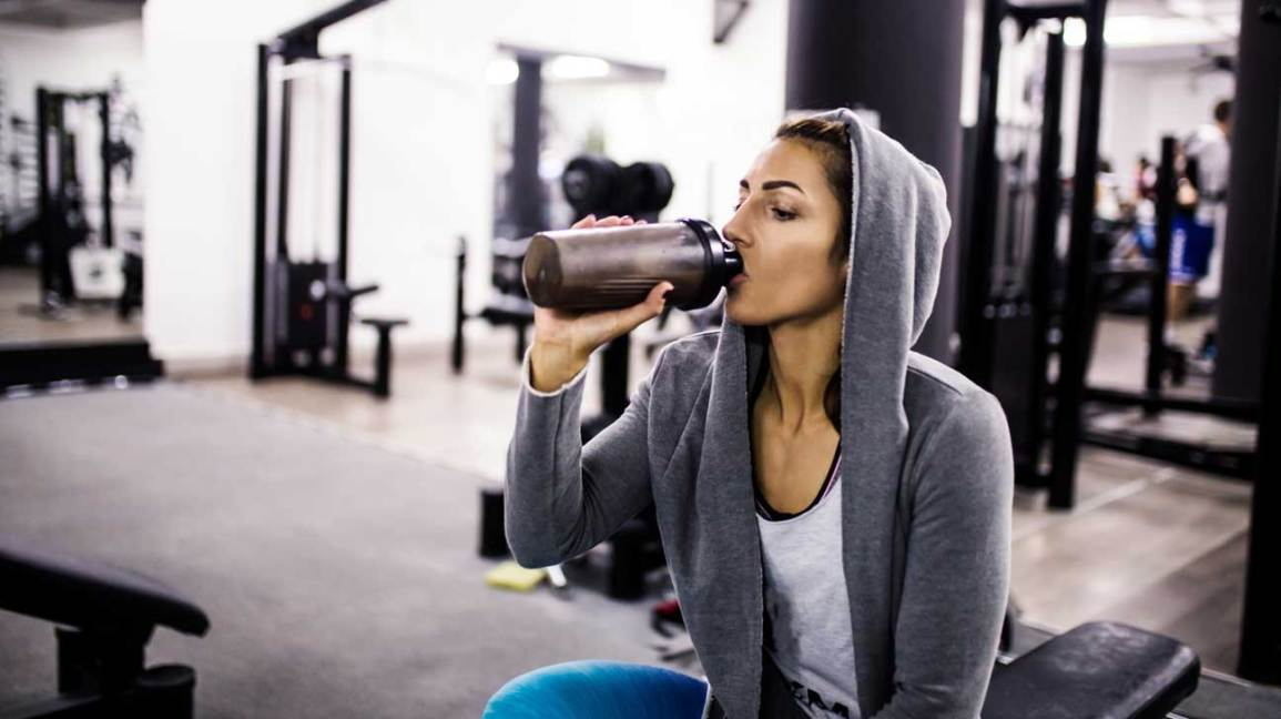 Woman in Gym Drinking a Protein Shake