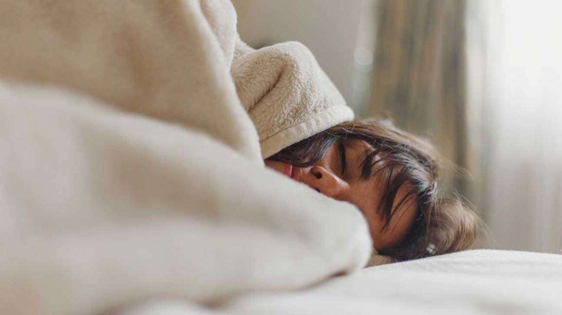 Woman Wrapped in Blanket in Bed