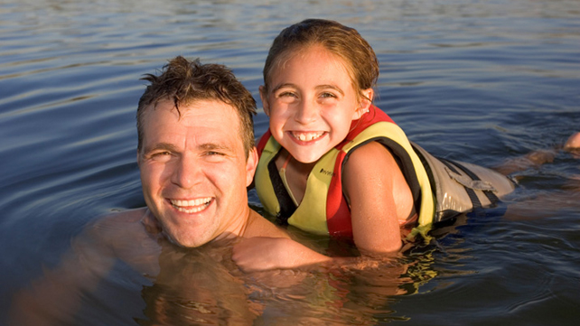 girl in life vest swimming with adult