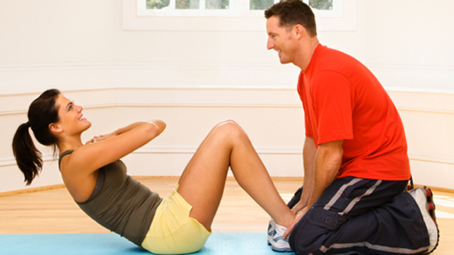 man helping woman do situps