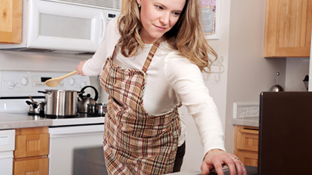 woman simultaneously at laptop and cooking