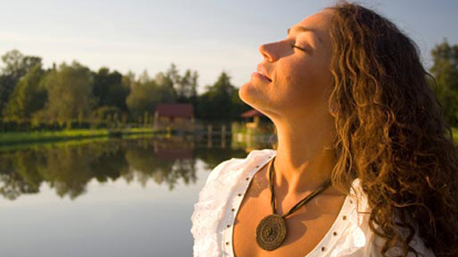 woman outdoors taking a deep breath