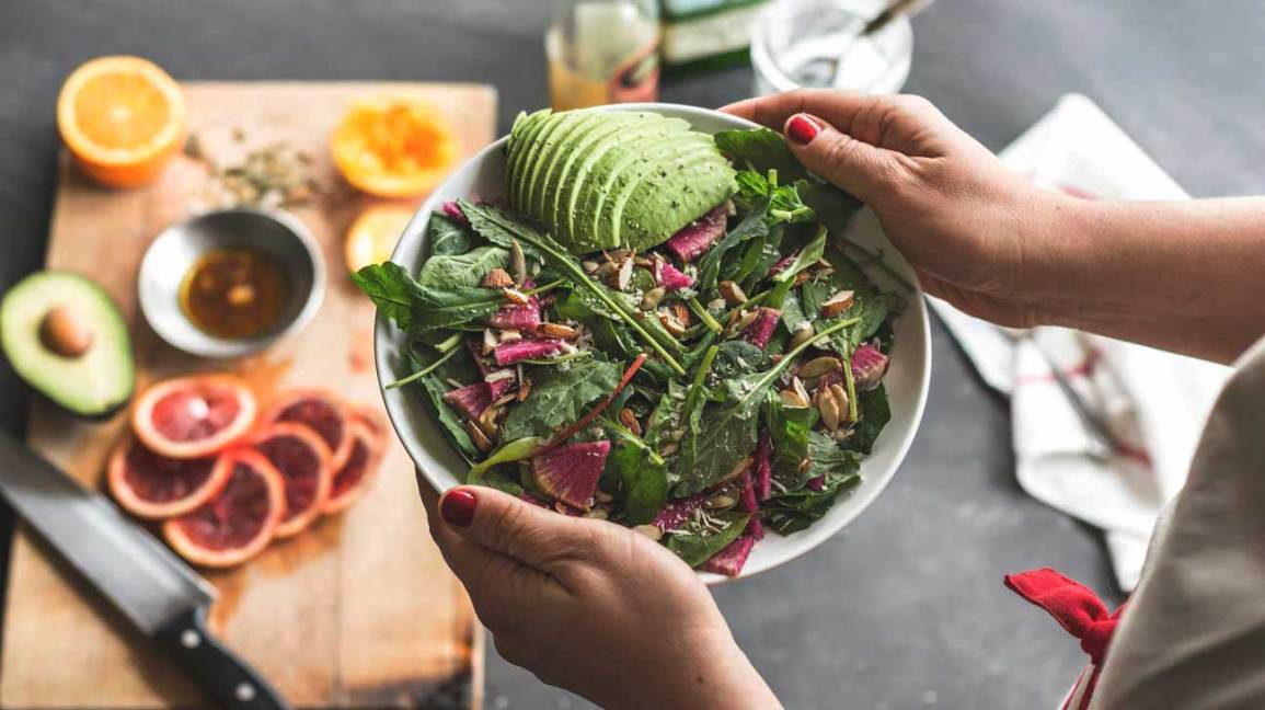 Hands Holding Salad With Avocado