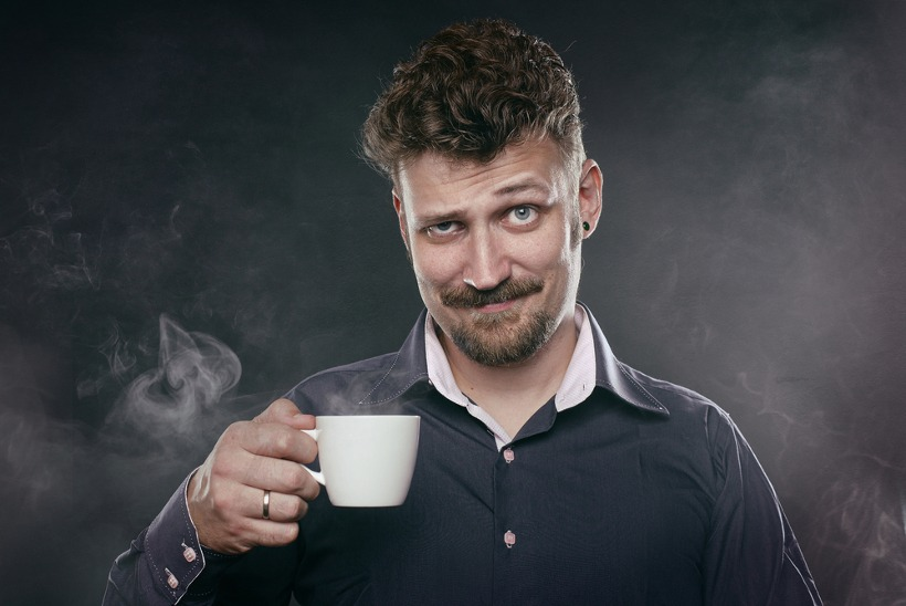 Skeptical Man Holding Cup Of Coffee