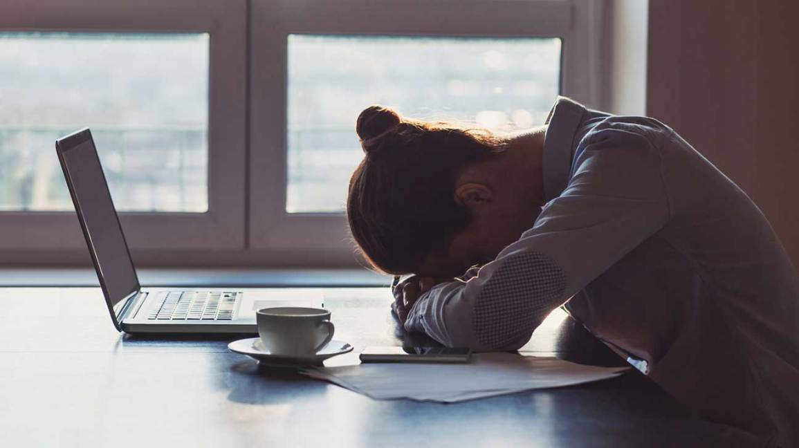 Tired Woman Resting Head on Desk
