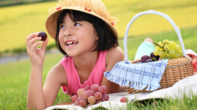 young girl snacking on grapes