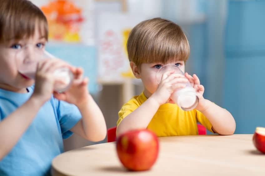Due bambini che bevono un bicchiere di latte