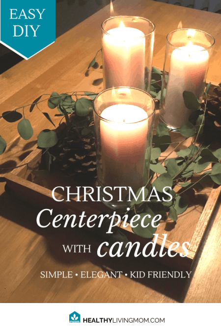I love to bring in some joy and warmth to our home by having a Christmas centerpiece with candles on our table throughout the season. And when I say season—it can stay out all winter. It's not too Christmas-y.  It's super fun to see people post their Christmas tours or Winter tours of their homes—but honestly, it's not all that realistic for young families.   So for us, we just try to keep things simple and family friendly.  This year, I used pretty much everything that we already had on hand to create this simple Christmas centerpiece with candles. It literally only cost me $6.  (picture)   My husband and I especially struggle with feeling seasonal depression most during this winter—so I've had to learn some ways to help us fight off those winter blues. And this is one way that I've found to really help.  I look for ways to combine fresh greenery and candles.  The best part about the greenery I used this year?  It's already cut and it dries really nicely. In fact, I've found a new love for working with fresh eucalyptus the past year.  For the candles, I've used real ones, but they are are friendly and safe for kids. I've either put them in large glass containers or candle holders that are closed. Another option is to use battery powered candles—but that's just not the same. I love real candles.  I've realized that just adding this simple Christmas centerpiece with candles to our home, it makes such a big difference. It's especially noticeable for us emotionally around the month of February—when winter seems to be dragging on for forever.  Here's my list of materials that I used this year—all of which we already owned.  1 Wood serving tray 3 Glass hurricane candle vases 2 Medium size white pillar candles 1 Large size white pillar candle 2 Large pine cones 1 fresh bunch of eucalyptus   The wood serving tray was my husband's grandmothers tray. This piece is the key to making this winter centerpiece family friendly and functional. What I love about it, is that it makes