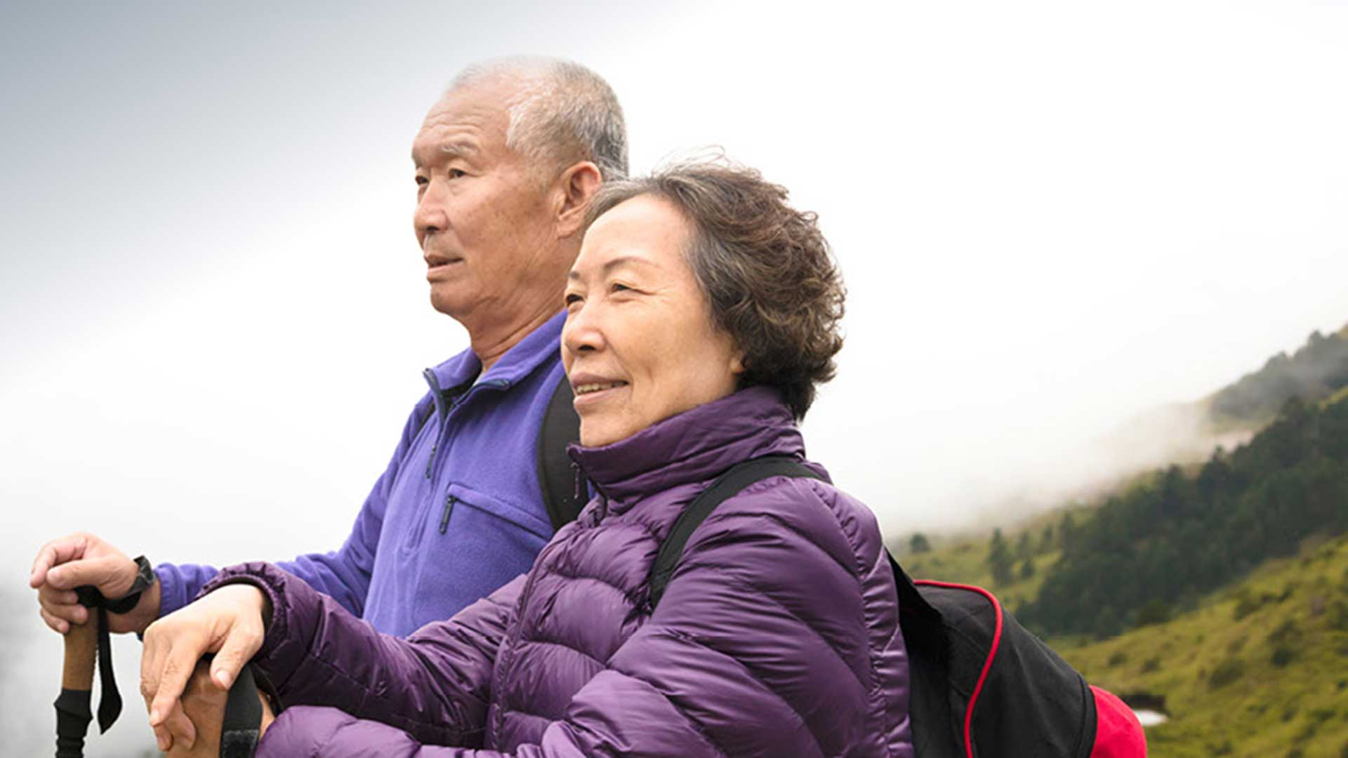 an elderly asian couple stand atop a mountain surrounded by fog, proud of overcoming hearing loss