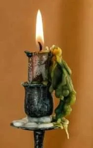 Lit candle in metal holder with green wax cascading down the side.