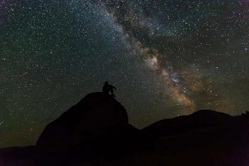 A man sitting on a rock silhouetted by the Milky Way.