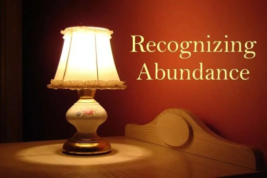 Lit lamp on a table with the title Recognizing Abundance.