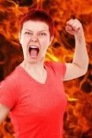 Angry woman with clenched fist against a background of flames.