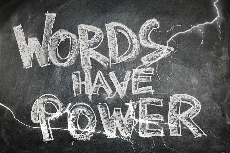 "A black chalkboard with ""words have power"" written in thick chalk lines."