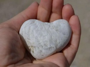 A hand offering a heart carved in stone.