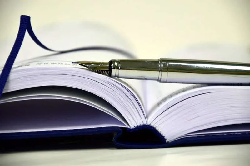 Open book with a fountain pen lying across its pages.