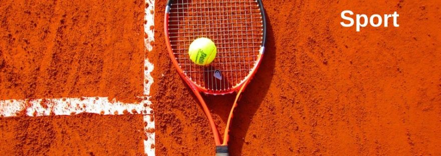 A tennis racket and ball lay on a clay court next to some white lines on the court