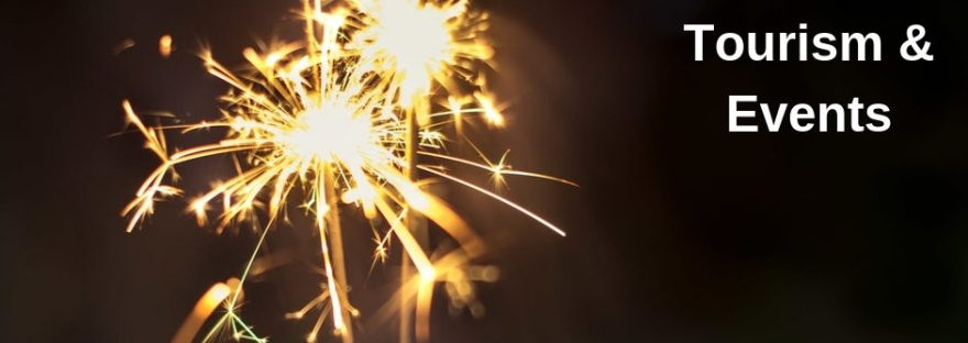 A sparkler of fire cracker sparkles against a dark background