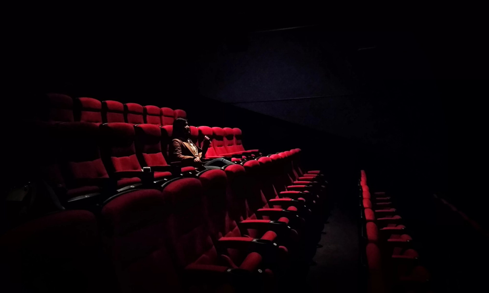 a woman sits alone in a theatre auditorium