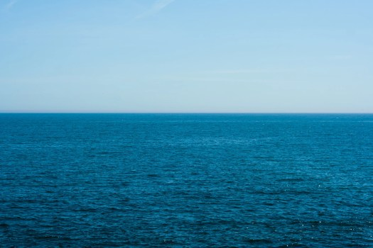 A calm, blue sea and cloudless sky