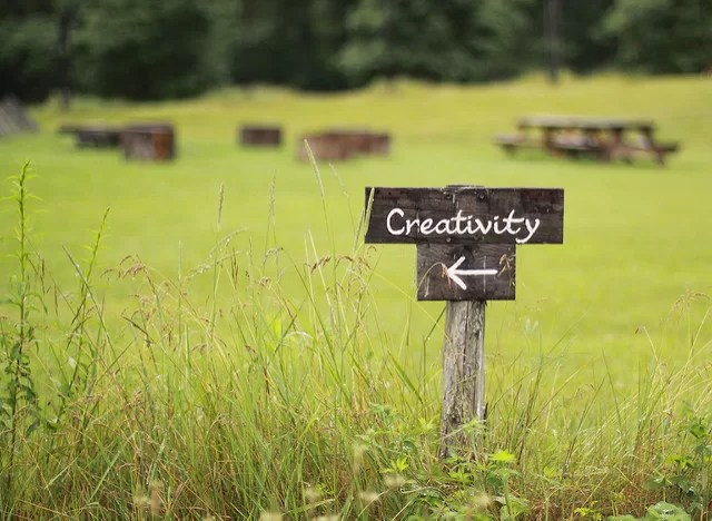 A wooden sign in a green field points to 'creativity'