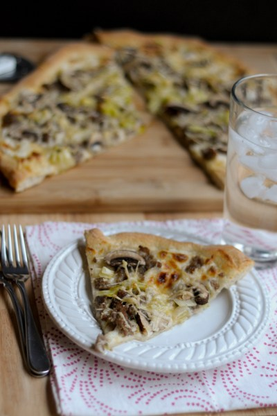 Sausage, Leek and Mushroom Pizza is a warm and comforting pizza to enjoy with friends. Crumbled pork sausage, butter-sauteed leeks, mushrooms and a bed of bechamel sauce are sure to please.