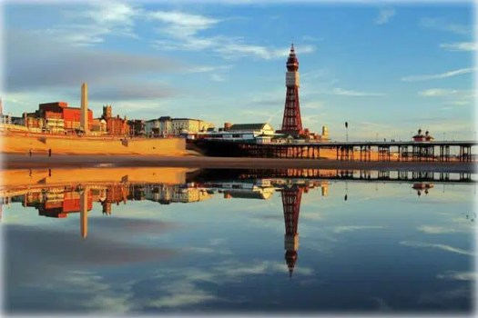 A Fylde Coast Golden Hour Reflection of Blackpool Tower and North Pier on a calm still early evening glow. Blackpool, England
