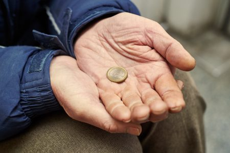 Beggar people and human poverty. Male hands of homeless person with one euro charity in city street
