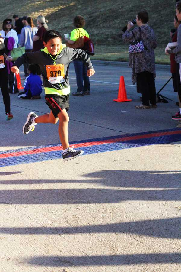 A young runner passes through the finish line.