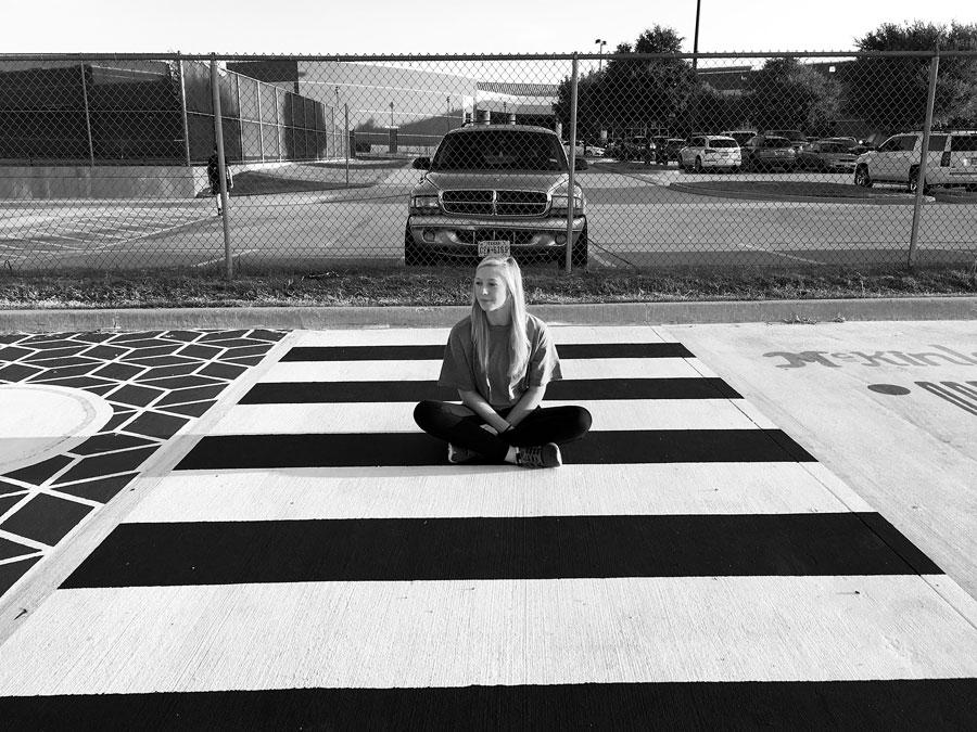 Senior Avery Crowe sits in her parking spot. Due to her relapse in late August of 2016, Avery lost memory of painting it.