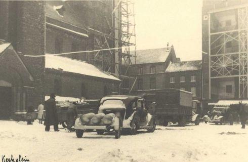 Bron: Rijckheyt.nl | Kerkplein (1942). De ruiten van het Glaspaleis (rechts) zijn beplakt met tape om beschadiging bij een bombardement te voorkomen. Om de toren van de St.Pancratiuskerk (links) is een steiger gebouwd door aannemer P.Meulenberg, die op last van de bezetter de klokken uit de toren moest halen.