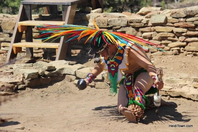 Aztec dancer at Native American Cultural Gathering in Colorado kneels. HeidiTown.com