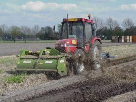 Voorop de traktor zit een klepelaar, achterop de traktor een veegmachine