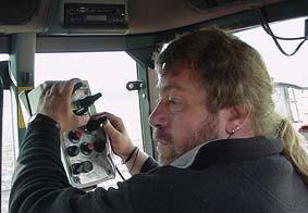 Chauffeur Monemans uit Weert, regelt tijdens het rijden(in de tractor) de juiste afstellingen van de rooimachine.