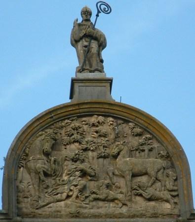 Statue und Jagdszene an der Fassade der Kirche in St-Hubert