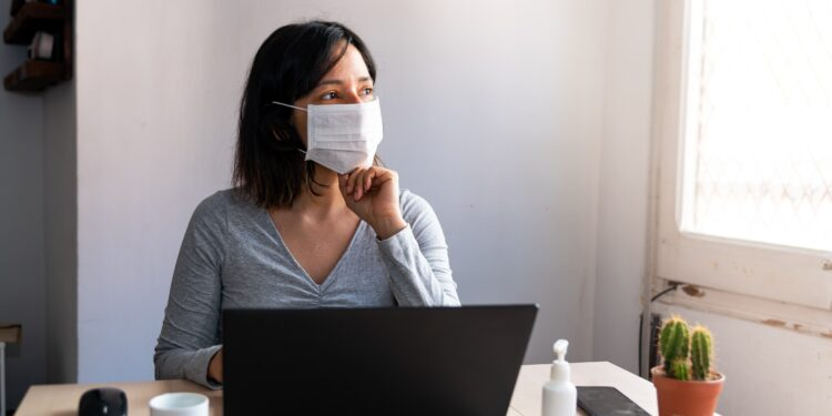 Woman with mouth and nose covering sits in front of her laptop and looks out the window