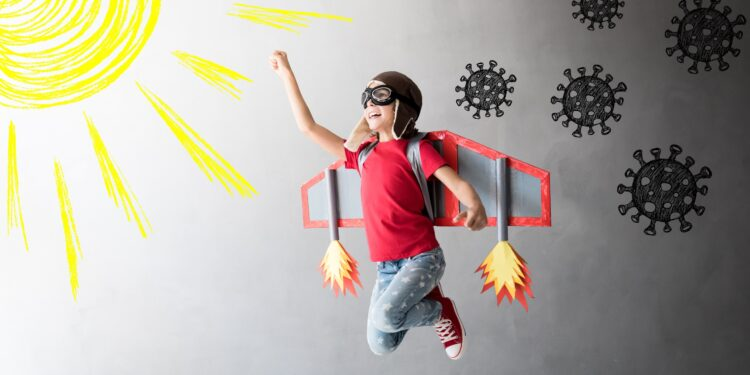 Child with airplane wings and circled by corona viruses jumps towards a drawn sun.