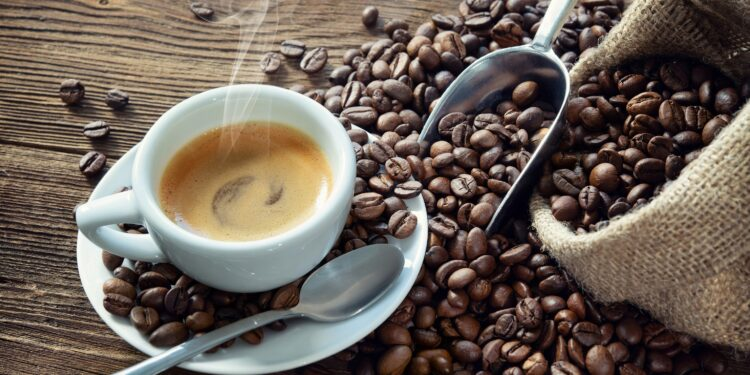 Image of coffee in cup together with coffee beans.
