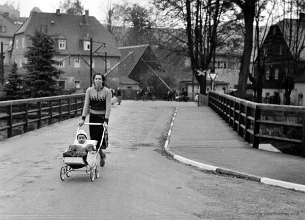 Frau mit Kinderwagen auf der Brücke.
