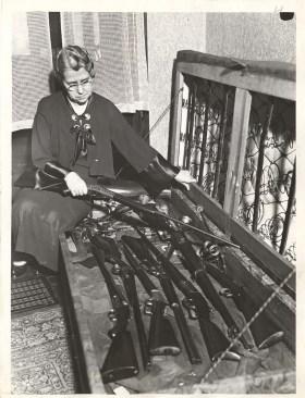 Unidentified woman with guns hidden under box frame mattress, c. 1930.   Heinz History Center