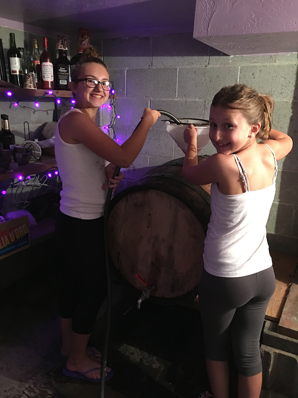 Two members of the Mancini family help siphon grape juice into a barrel for aging. Courtesy of the Mancini family.