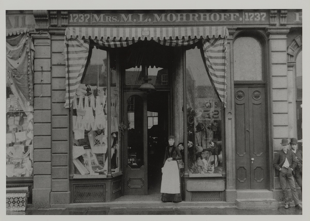 Mary L. Mohrhoff posing in front of her millinery and dressmaking shop on Carson Street
