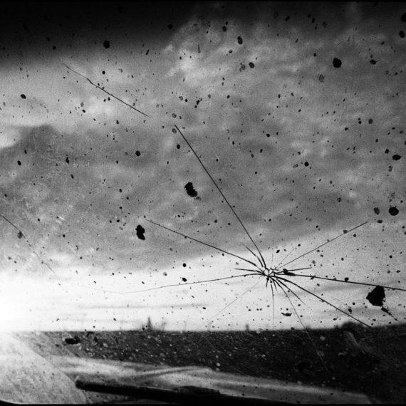 'Cracked Window #1, Palo Duro, Texas, 1983' © Chris Bartlett. black and white Polaroid - cracked Window of a truck