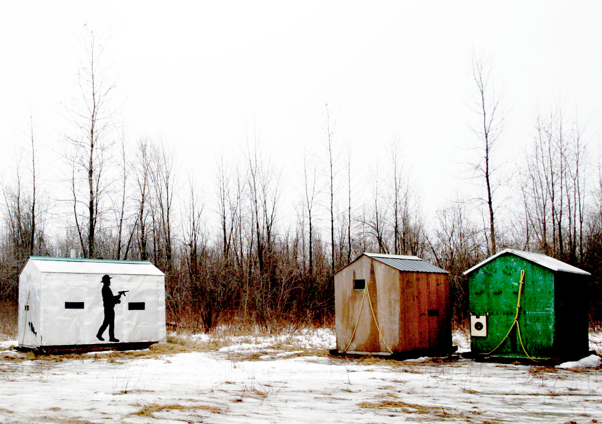 Jason Florio photography - color image of Ice Fishing Sheds, Canada, one shed has a silhouette of a cowboy holding a gun