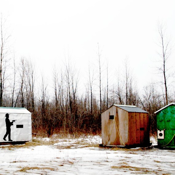 ©Jason Florio 'Ice Fishing Sheds Canada'. Color - 3 painted sheds in a winter forest setting