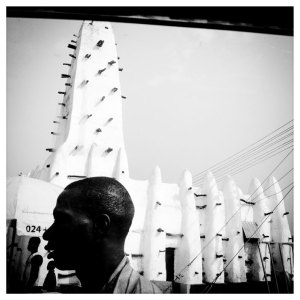 Black and white image of man in front of mosque, West Africa 'White Mosque', Ghana © Jason Florio