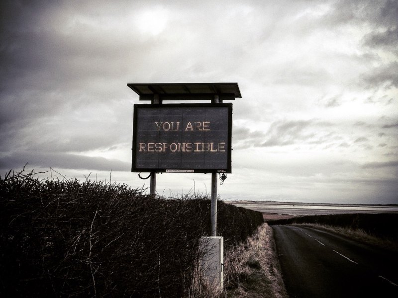Image by Helen Jones-Florio of the neon warning sign at the head of the causeway onto Holy Island, Northumberland, UK