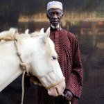 ©Jason Florio -' Herouna with his White Horse,' The Gambia. Color portrait of village chief, or Alkalo, against black cloth