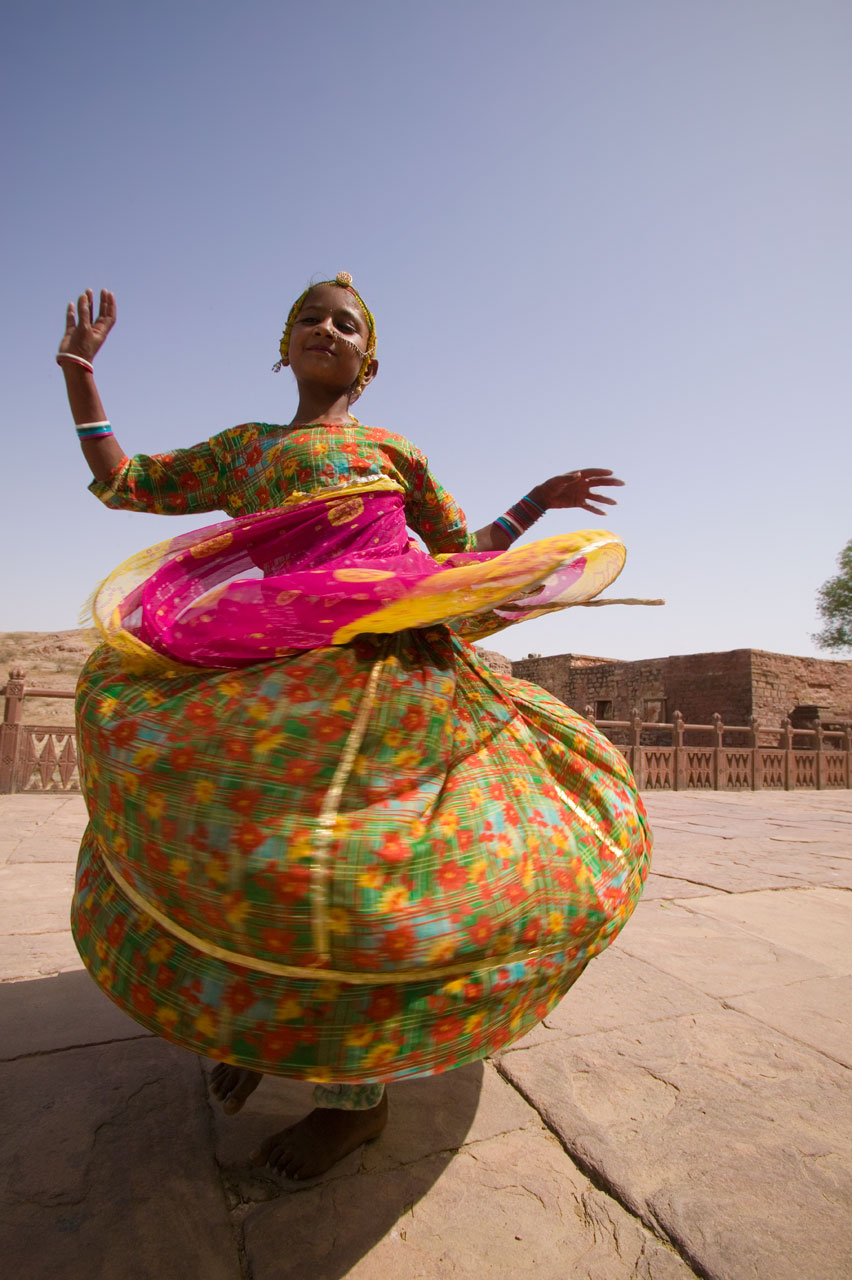 Jason Florio photography -color image of a young Indian Girl, dressed for a celebration, spins around in her long dress, billowing out, India